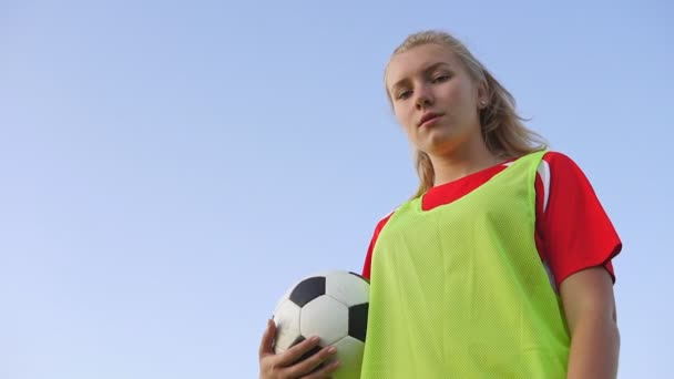 Bottom view portrait of a confident teen girl football player with a soccer ball