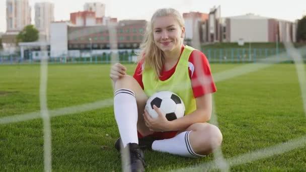 Porträt einer lächelnden süßen Fußballerin, die mit Fußballball auf dem Feld sitzt