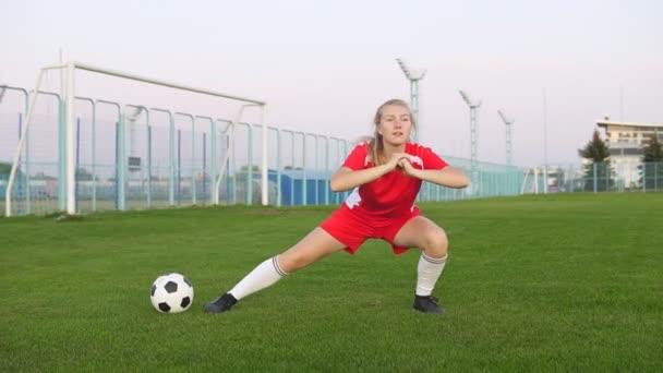 junge Fußballerin beim Stretching auf dem Fußballplatz mit grünem Gras
