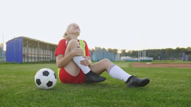 Dívčí fotbalista, který sedí v trávě za zranění