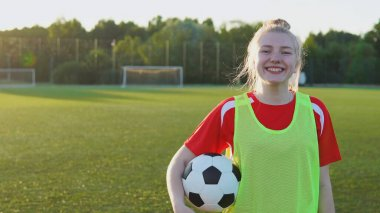 Portrait of a smiling teen girl football player with a soccer ball at sunset, copyspace
