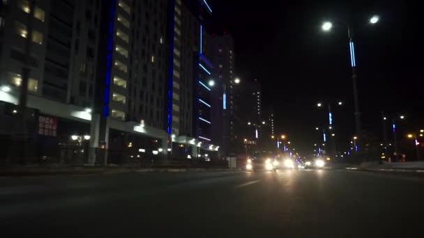 Pohled na rychlé auto pohybující se na noční avenue ve městě, silnice se světly odrážejícími se na autě na vysoké rychlosti. Záběry. Rychlý rytmus moderního města.