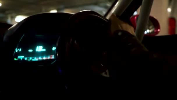 Blick in ein Auto und den fahrenden Mann. Verfilmung. Nahaufnahme der Hände des Fahrers am Lenkrad eines Autos, das in der Tiefgarage vorbeifährt.