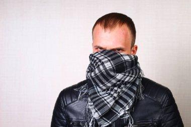 A man in a leather jacket, biker, rocker on a blurred background wall
