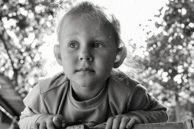 Şirin, sevimli, gülümseyen beyaz beyaz bir çocuğun siyah beyaz portresini kapat. Doğada mutlu bir çocuğun portresi. Mutlu çocukluk kavramı. Bebek kameraya bakıyor. Çocuğun samimi duyguları