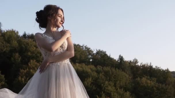 Mladá krásná dívka s černými vlasy v bílých bujných šatech a vlasy stojí na pozadí lesa a oblohy a hladí jeho ruku na rameni a druhá ruka se drží v pase a dívá se do dálky