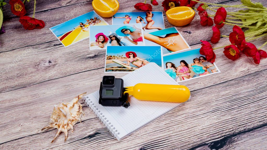 Action camera gopro and lots of pictures of girls on the beach on a wooden table