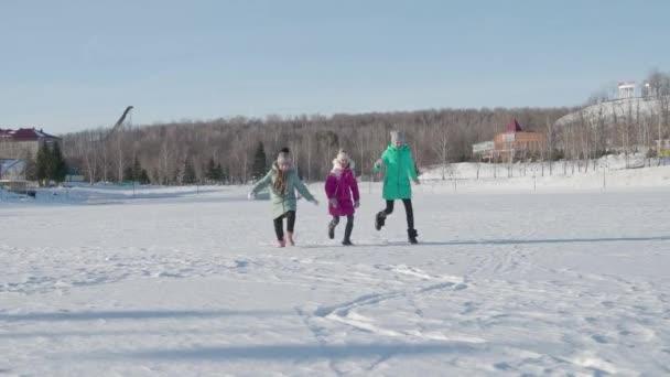 Tři děti zábavné běhu v parku v zimě