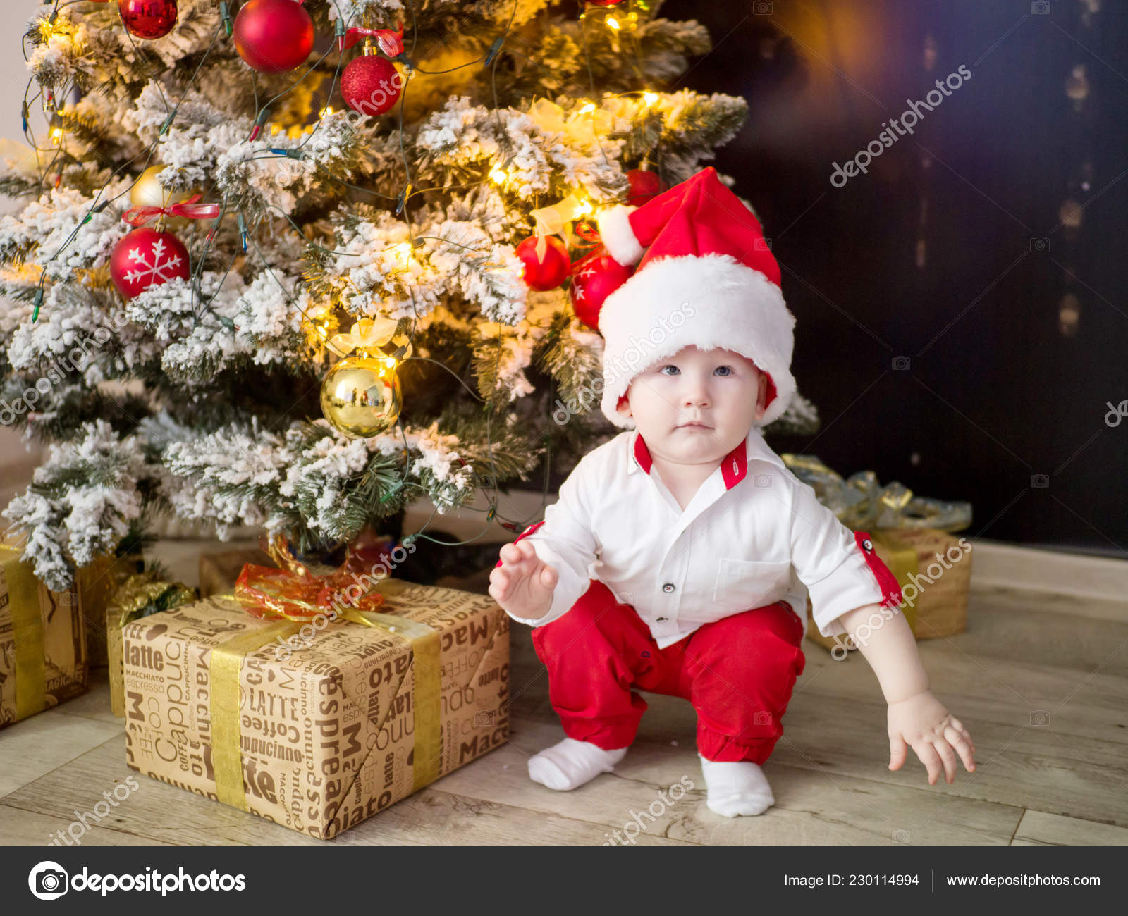 A Small Child In A Red Santa Hat Under An Elegant Christmas Tree With Lights And Balls At Home Stock Photo Image By C Dina777 230114994