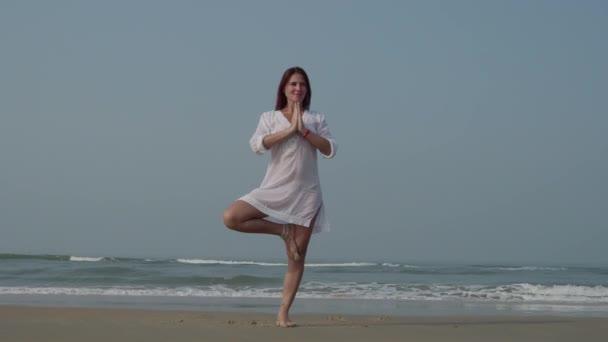 Mladá běloška cvičení jógy v mořské vodě nebo oceánu. Krásný odraz. Komplex ásany, rovnováhu. Fitness, sport, jóga a koncept zdravého životního stylu. 4k