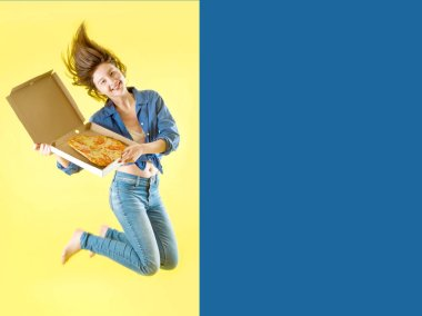 Smiling young girl or girl in jeans and a blue shirt is having fun jumping high while holding a pizza box in hands on a yellow background