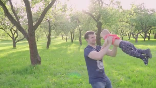 Young father playing with his son, throws him up, circling