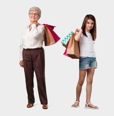 Full body of an elderly lady and her granddaughter cheerful and smiling, very excited carrying a shopping bags, ready to go shopping and look for new offers