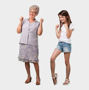 Full body of an elderly lady and her granddaughter very happy and excited, raising arms, celebrating a victory or success, winning the lottery