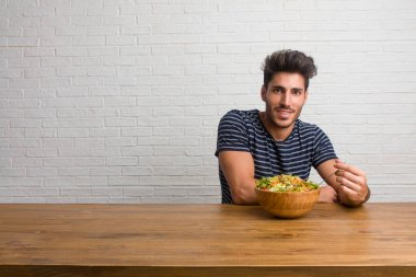 Young handsome and natural man sitting on a table with hands on hips, standing, relaxed and smiling, very positive and cheerful. Eating a fresh salad.