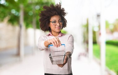 black woman holding shopping basket, selective focus