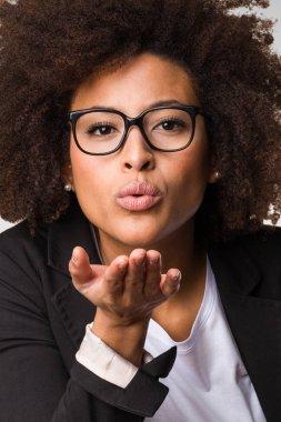 black business woman sending kisses on gray background