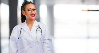 Portrait of a young black doctor woman cheerful and with a big smile, confident, friendly and sincere, expressing positivity and success