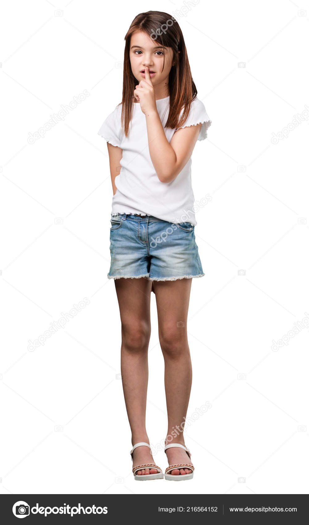 Full body little girl keeping secret asking silence serious face stock photo
