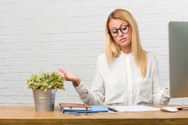 Portrait of young student sitting on her desk doing tasks doubting and shrugging shoulders, concept of indecision and insecurity, uncertain about something