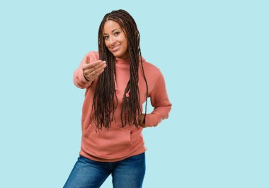 Portrait of a young black woman wearing braids inviting to come, confident and smiling making a gesture with hand, being positive and friendly