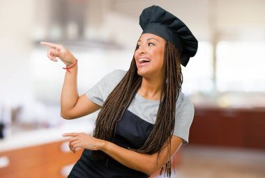 Portrait of a young black baker woman pointing to the side, smiling surprised presenting something, natural and casual