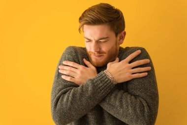 Young redhead man face closeup going cold due to low temperature