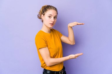 Young caucasian woman on purple background shocked and amazed holding a copy space between hands.