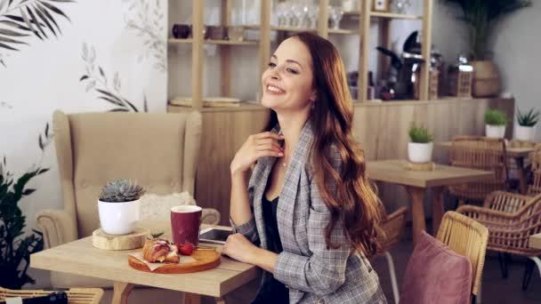 portré egy vonzó fiatal nőről, aki egy kávézóban ül. Kávézó városi életmód. Véletlen portré