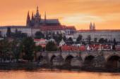 Pražský hrad a Karlův most při západu slunce s řekou Vltavou