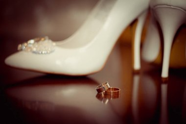 Wedding accessories. Wedding rings and bridesmaid shoes.
