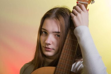 Portrait of a young girl with a guitar. Emotion concept. Photo on a pink-yellow background in neon colors.