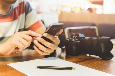 Mans hands using smart phone with DSLR camera and pen over paperwork on wooden table.