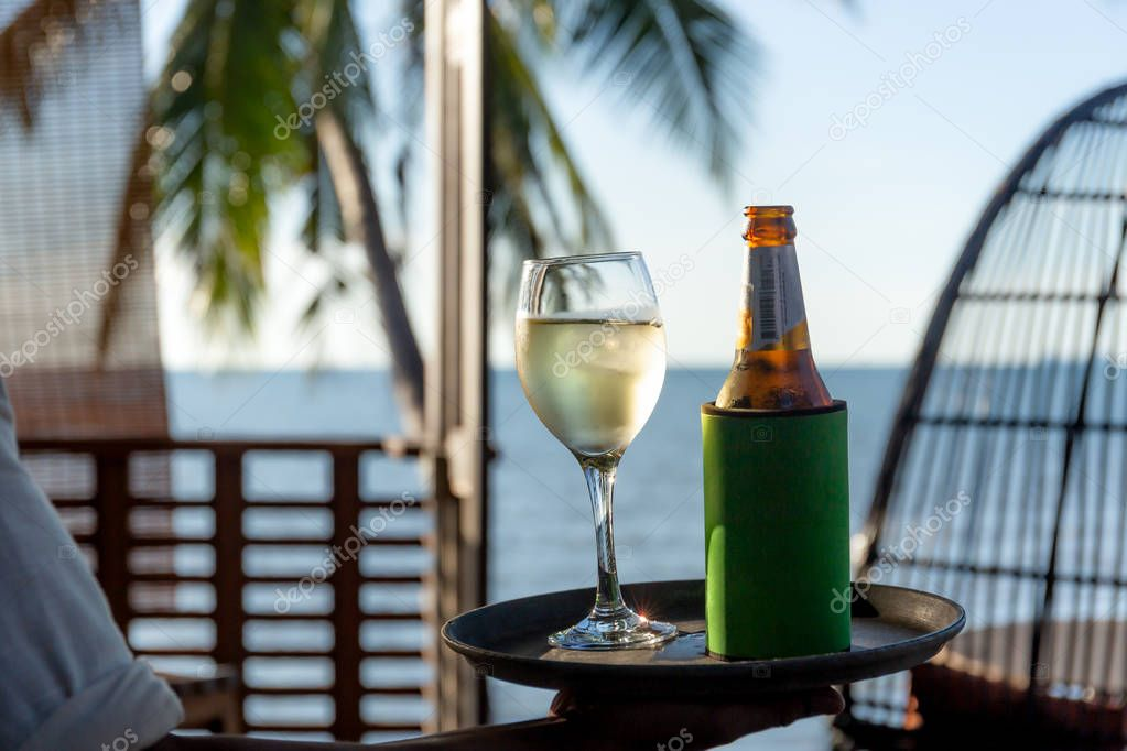 Waiter seaving glass of white wine and bottle of beer on a tray by the beach