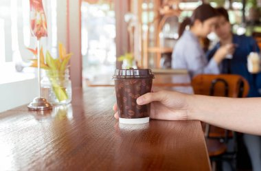 Woman hand holds out a paper cup of coffee to take away