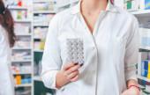 Pharmacist holding medicine in drugstore