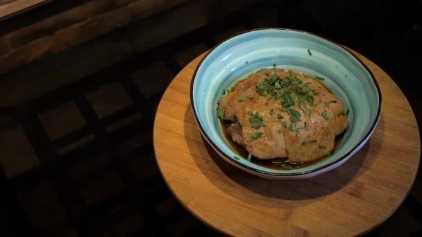 Leckeres Fleischgericht rotiert auf dem Holzteller vor dunklem Hintergrund.