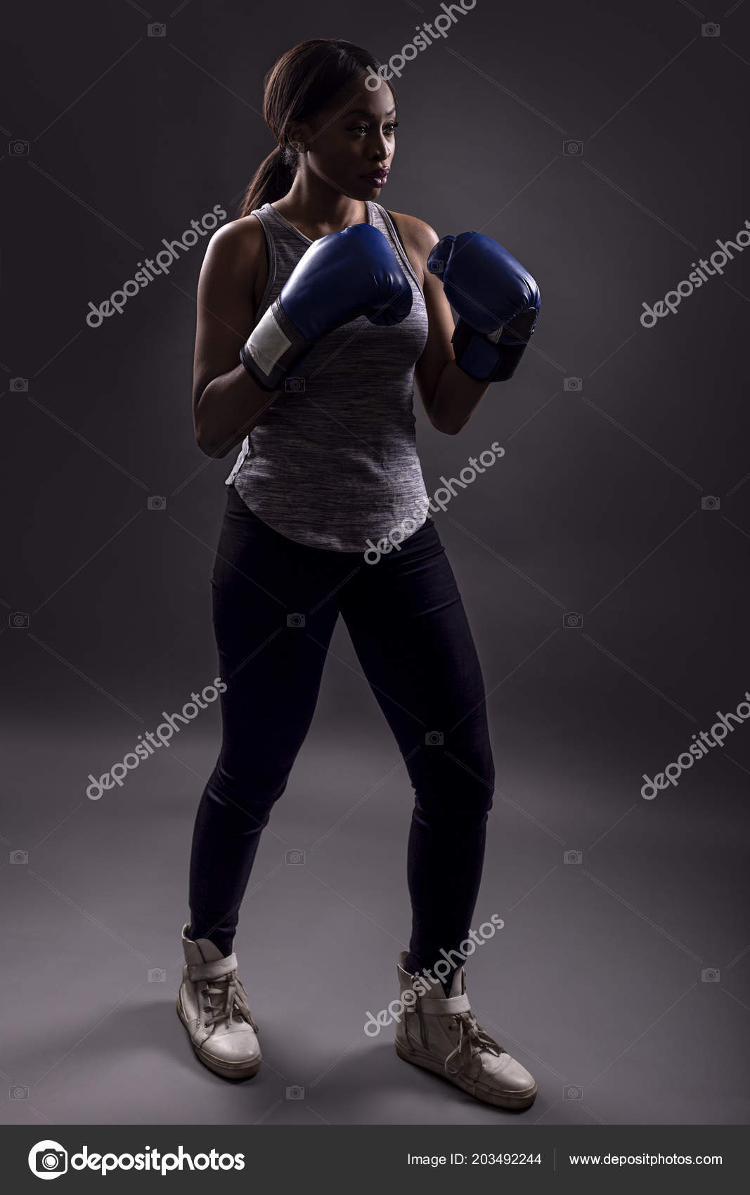 Partial Silhouette Athletic Black Female Wearing Boxing Gloves