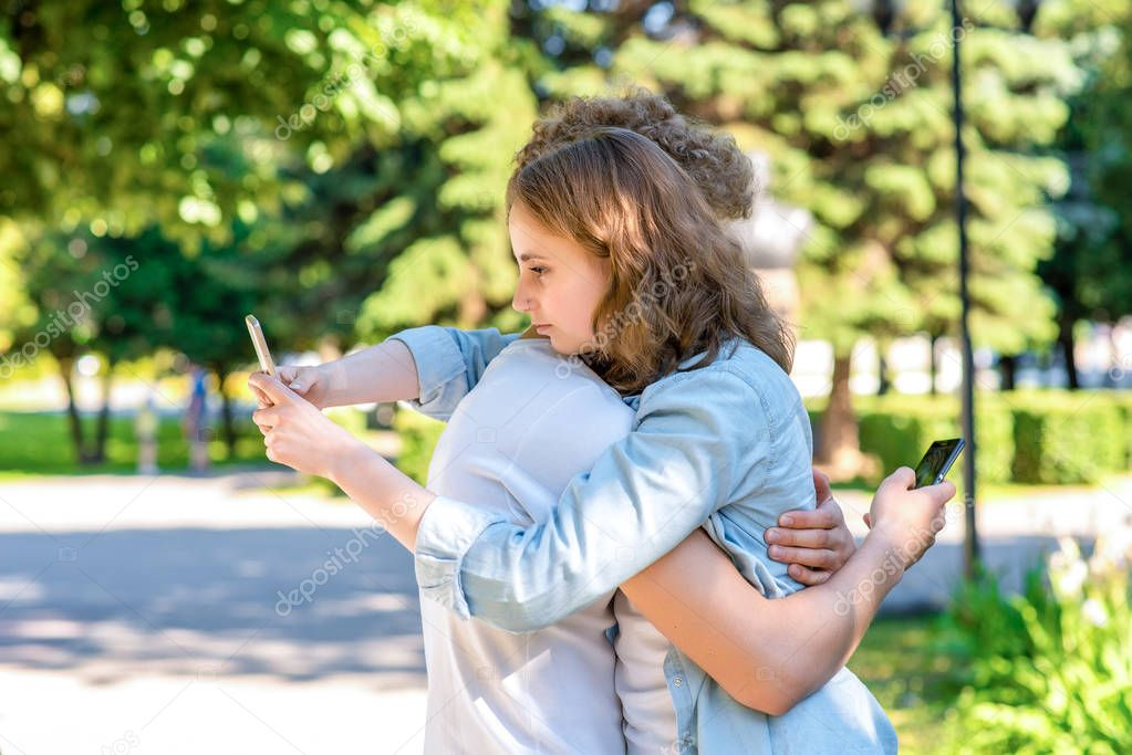 The guy with the girl hugs. Summer in nature. In the hands of holding smartphones. To correspond in social networks. The concept of trust is happiness together. The beginning of the relationship.