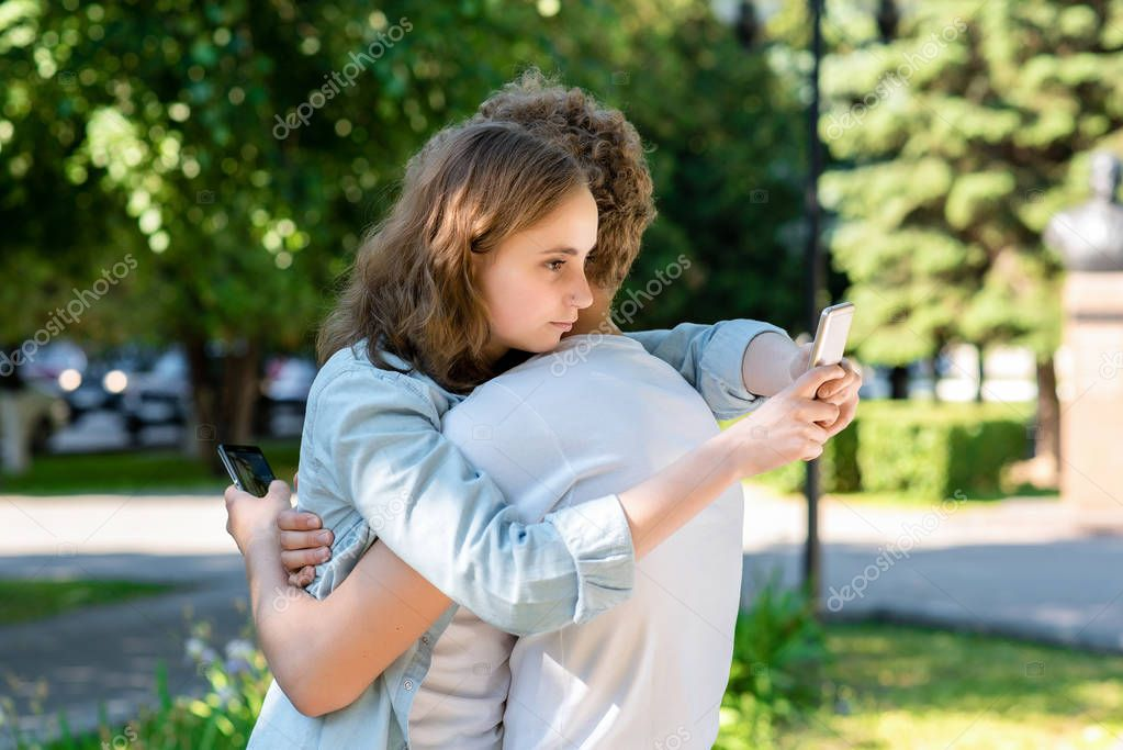 The girl hugs a guy in summer in nature. In the hands of holding smartphones communicates in social networks. Students after school rest. Happy beginning of the relationship. Best friends forever.