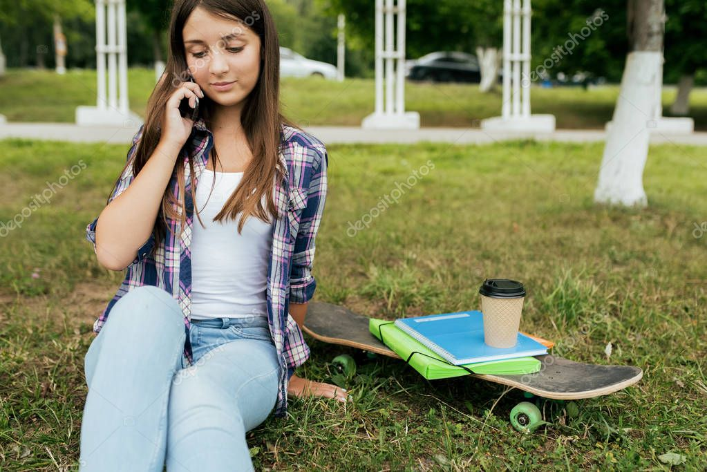 Girl schoolgirl after class, sitting on the grass, next to a skate textbooks cup of tea. Calls by phone, communicates in social networks.