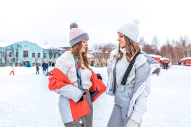Two girls girlfriends in winter in the city in jackets, stand in overalls in sweaters and warm hats, on a city skating rink. Happy smiling people holding hands, relaxing on weekends.