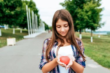 Girl schoolgirl 13-16 years old stands in summer city hands toy heart. Free space text. Happy smiles. Concept donation, blood life, gift, Valentines Day. Help and donation of organs in hospital.