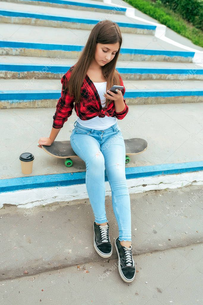 Girl schoolgirl 13-16 years old sits on a skateboard stairs in her hand phone, a cup of coffee tea. Online chat application in social networks, prints and watches videos on your smartphone.