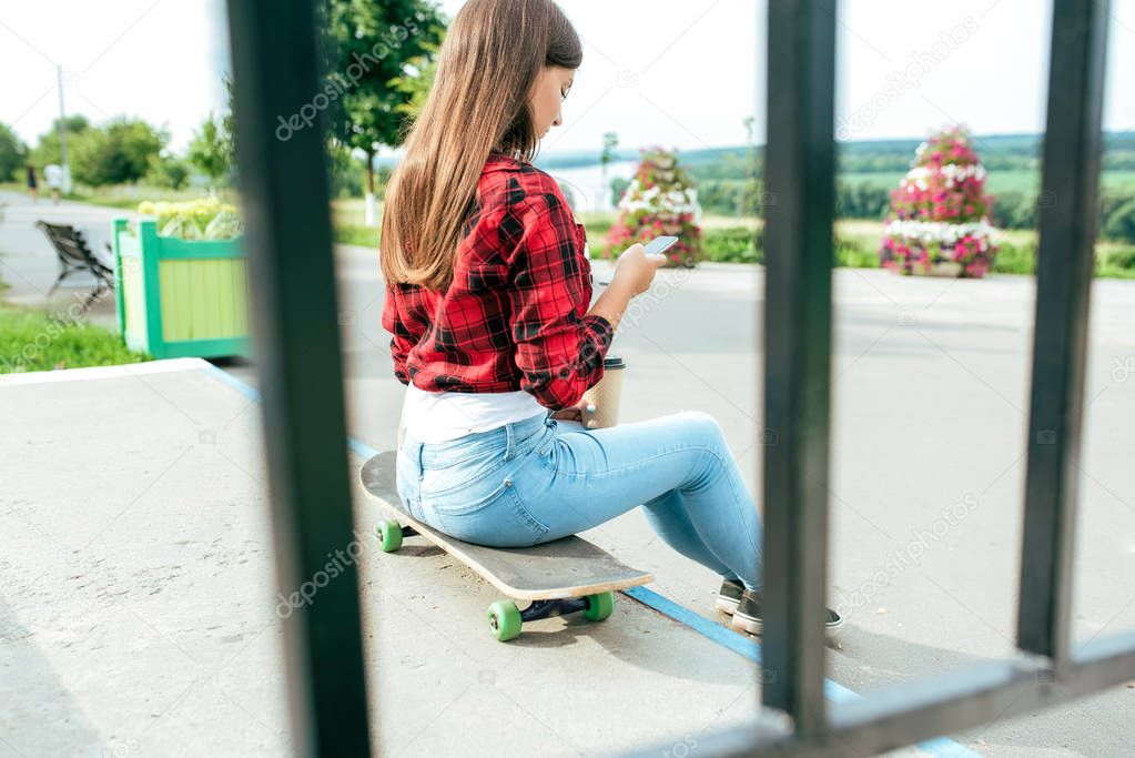Girl schoolgirl 13-16 years old sits on skateboard stairs in her hand phone. Online chat application in social networks, prints and watches videos on your smartphone. Railing fence on the background.