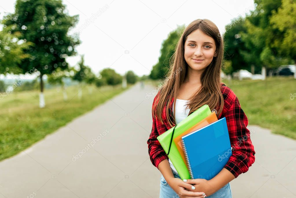 Girl schoolgirl 13-16 years old is in summer in city in a notebook textbooks folders. Free space for text. Happy smiling, resting after school, emotions of joy and fun after classes at institute.
