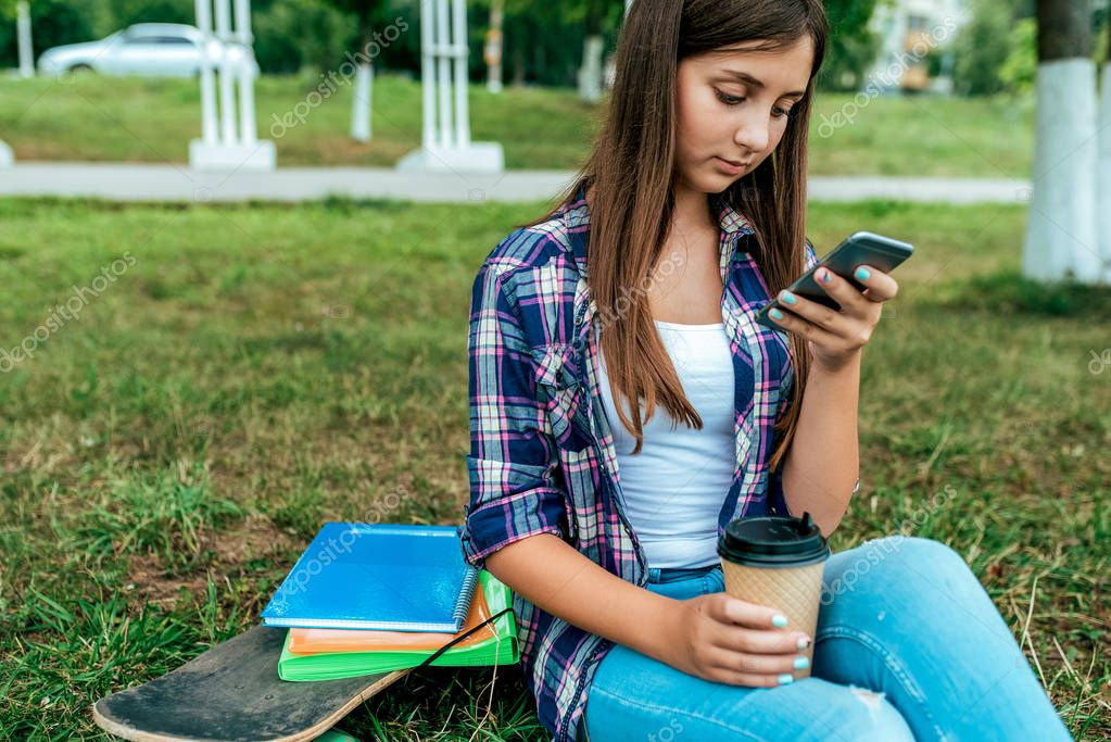 Girl schoolgirl 13-16 years old sits grass summer city park writes phone. Free space for text. Documents books notebook, cup coffee tea. Online application in social networks, Internet in smartphone.