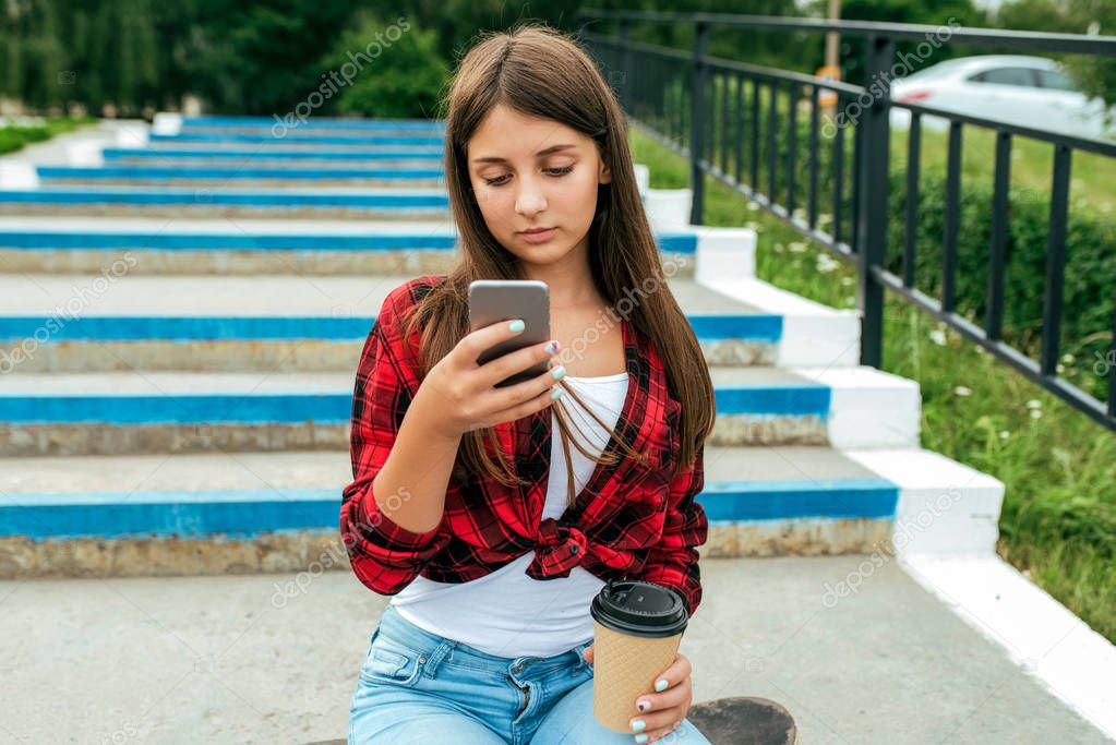 Schoolgirl girl teen 13-16 years old, sitting on a skateboard steps. In summer in city after school, in the hand smartphone, a glass of drink. Reads and looks application internet, social networks.