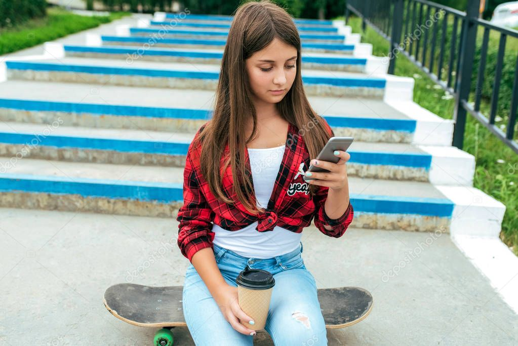 Girl schoolgirl sits on a skateboard, in her hands holds a smartphone, writes a message on social networks. Near a cup of tea.