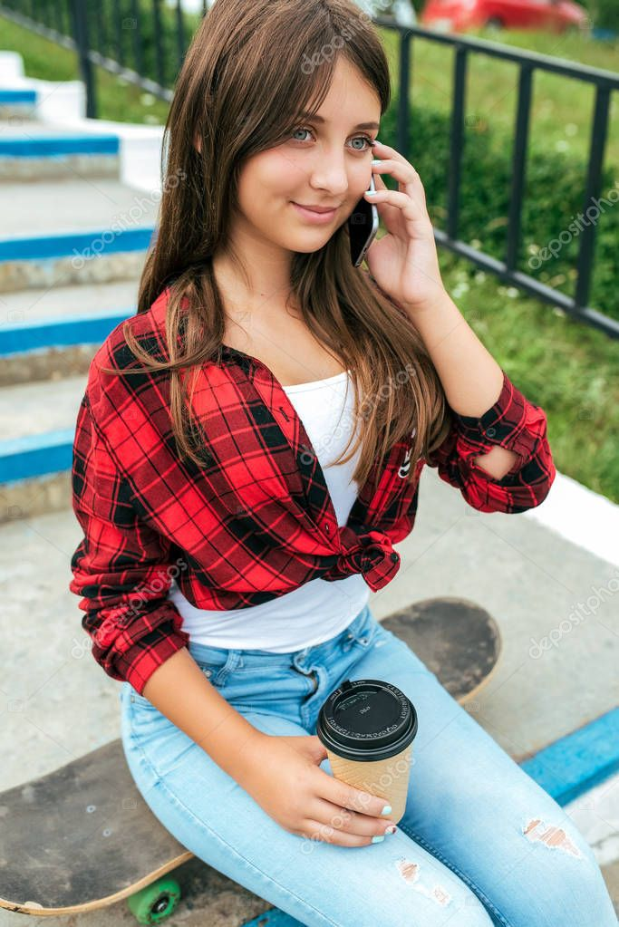 A girl calling on mobile phone a brunette schoolgirl sitting in summer in city on background of steps. Communication in Internet, application of social networks. In hands of a cup of coffee.